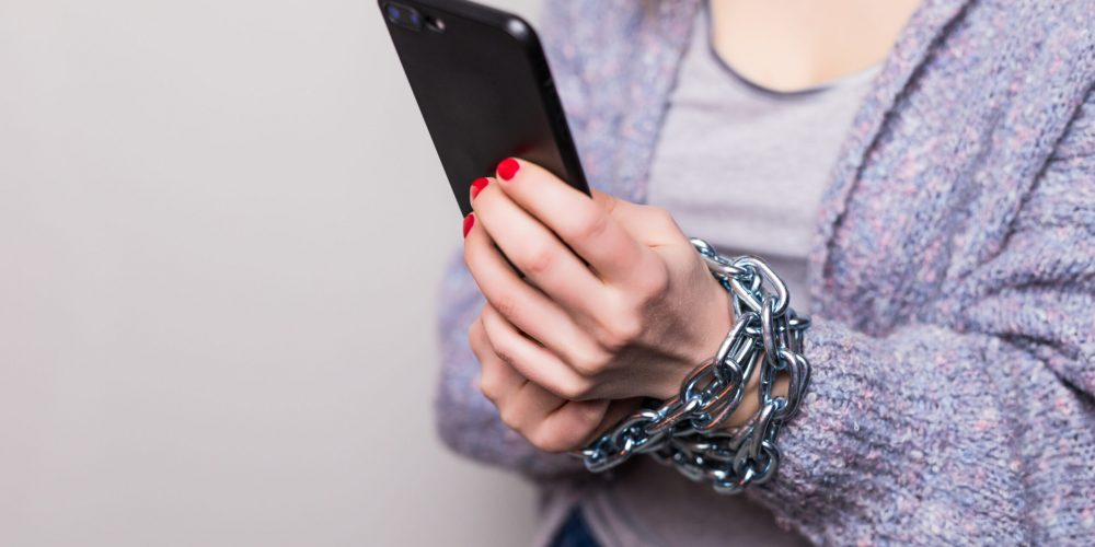 Girl with chain locked hands using a smartphone isolated on white background